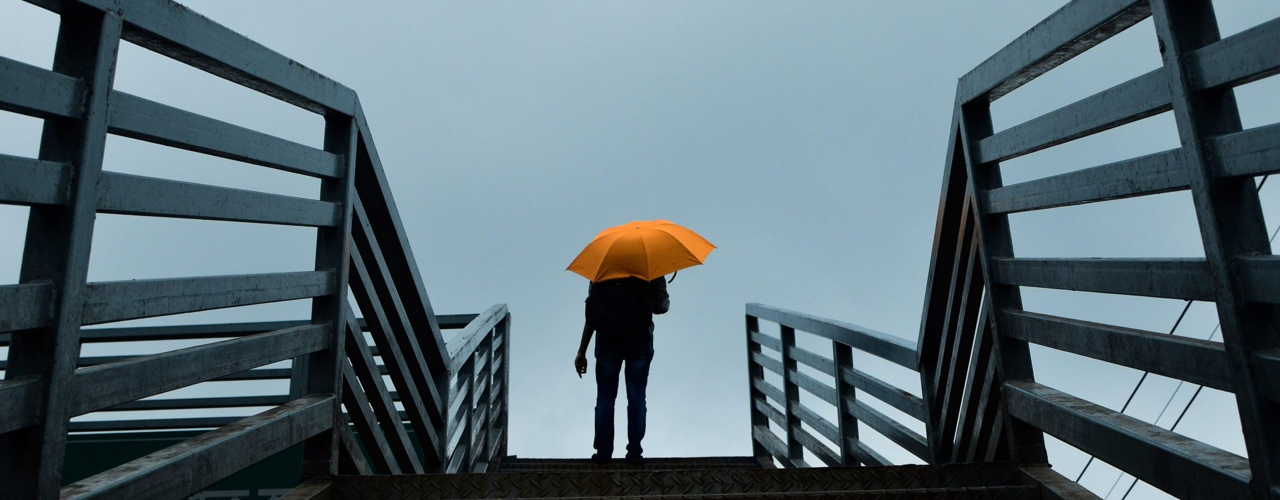 person-holding-umbrella-standing-above-stairs-1695056